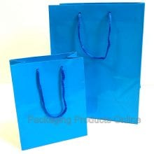 A small and medium sized glossy blue gift bag with blue cord handles.